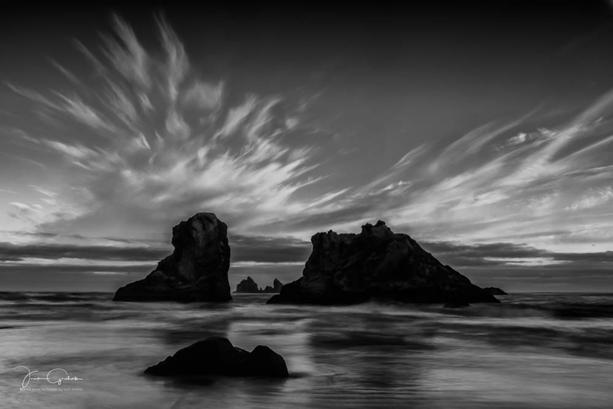monochrome image beach clouds rocks